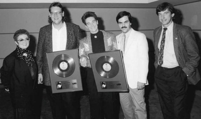 """k.d. lang with a Gold Record for """"Shadowland,"""" circa late 1980s in Toronto. Pictured l-r: Jo Bergman, Warner Bros. Vice-President Video, Larry Wanagas (k.d.'s manager at the time), k.d. lang, the late Randy Sharrard, Ontario Promotion, and Dave Tollington, Domestic Production Manager. Photo: Library and Archives Canada."""