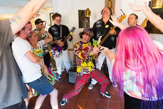 Mint Records fixture Nardwuar (middle) helps the gang celebrate