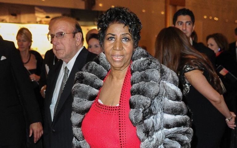 Aretha accompanied by Clive Davis. Credit: WENN.com
