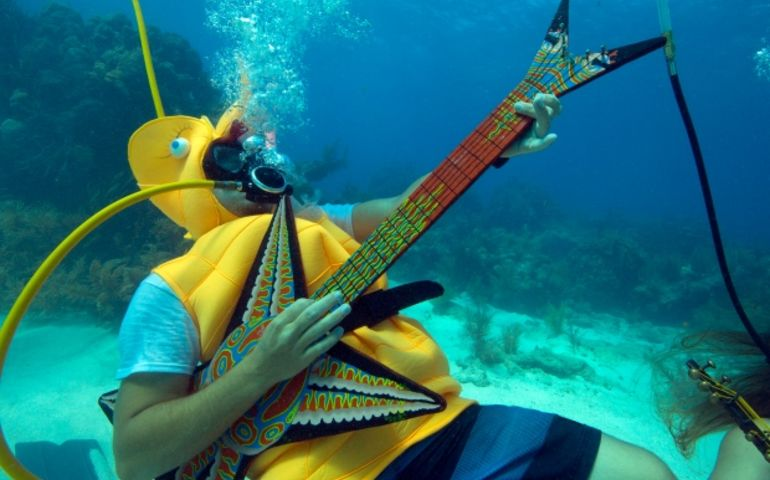 In this photo provided by the Florida Keys News Bureau, Jeff Wright, costumed as a seahorse, rocks with a fake guitar, Saturday, July 8, 2017, during the Underwater Music Festival in the Florida Keys National Marine Sanctuary off Big Pine Key, Fla. (Bob