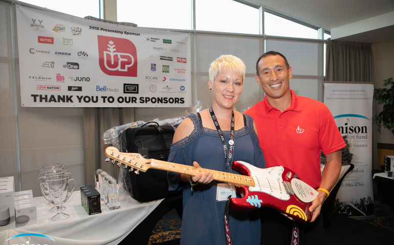 Unison ED Amanda Power and Newstrike / Up Cannabis' Peter Hwang pose with a special edition guitar, in commemoration of the company's $150K donation to the charitable fund at the CEC Golf classic on Wednesday.