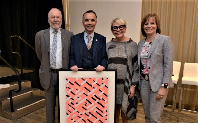 Gary Slaight, Daniele Zanotti, Emmanuelle Gattuso, and Beth Wilson hold an #UNIGNORABLE poster representing social isolation, at United Way's AGM — photo credit: Nicholas Jones.