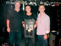 Following an enthusiastically received set previewing material from his new LP, Blue Highways, Colin James was presented 'Road Gold' by CIMA president Stuart Johnston (r) for his sterling career that had its start in 1988. With him on stage, True North topper Geoff Kulawick who has the record.