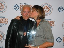 Murray McLauchlan receives an extra honour from wife Denise at his CCMA induction on Saturday. Photo: Wayne Newton