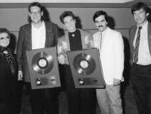"k.d. lang with a Gold Record for ""Shadowland,"" circa late 1980s in Toronto. Pictured l-r: Jo Bergman, Warner Bros. Vice-President Video, Larry Wanagas (k.d.'s manager at the time), k.d. lang, the late Randy Sharrard, Ontario Promotion, and Dave Tollington, Domestic Production Manager. Photo: Library and Archives Canada."