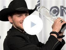 Brett Kissel holds one of his many trophies