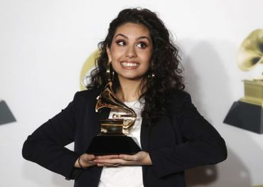 Alessia Cara holding her Grammy