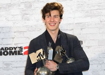 Shawn Mendes with his awards for Best Song and Best Artist backstage at the 2017 MTV EMA in London on Sunday. (Vianney Le Caer/Invision/Associated Press)
