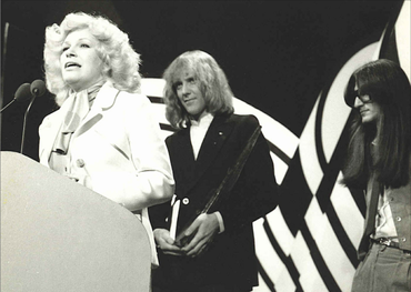 Carroll Baker at the podium after being presented her Juno Award by members of Rush