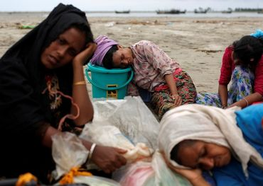 Exhausted Rohingya refugees rest on the shore after crossing the Bangladesh-Myanmar border by boat through the Bay of Bengal in Shah Porir Dwip, Bangladesh, September 10, 2017. Reuters