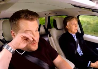 James wiping away a tear at tthe wheel of the car with Sir Macca sitting next to him.